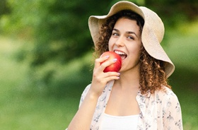 Eating apple and enjoying benefits of dental implants in Plymouth