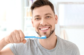 Smiling man brushing teeth to maintain dental implants