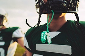 Green mouthguard hanging from football helmet