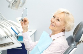 senior woman admiring dentures