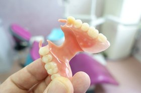 hand holding partial denture