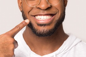 Man pointing at healthy smile with single dental implant