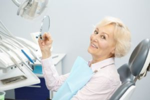 Happy patient after transitioning from dentures to dental implants